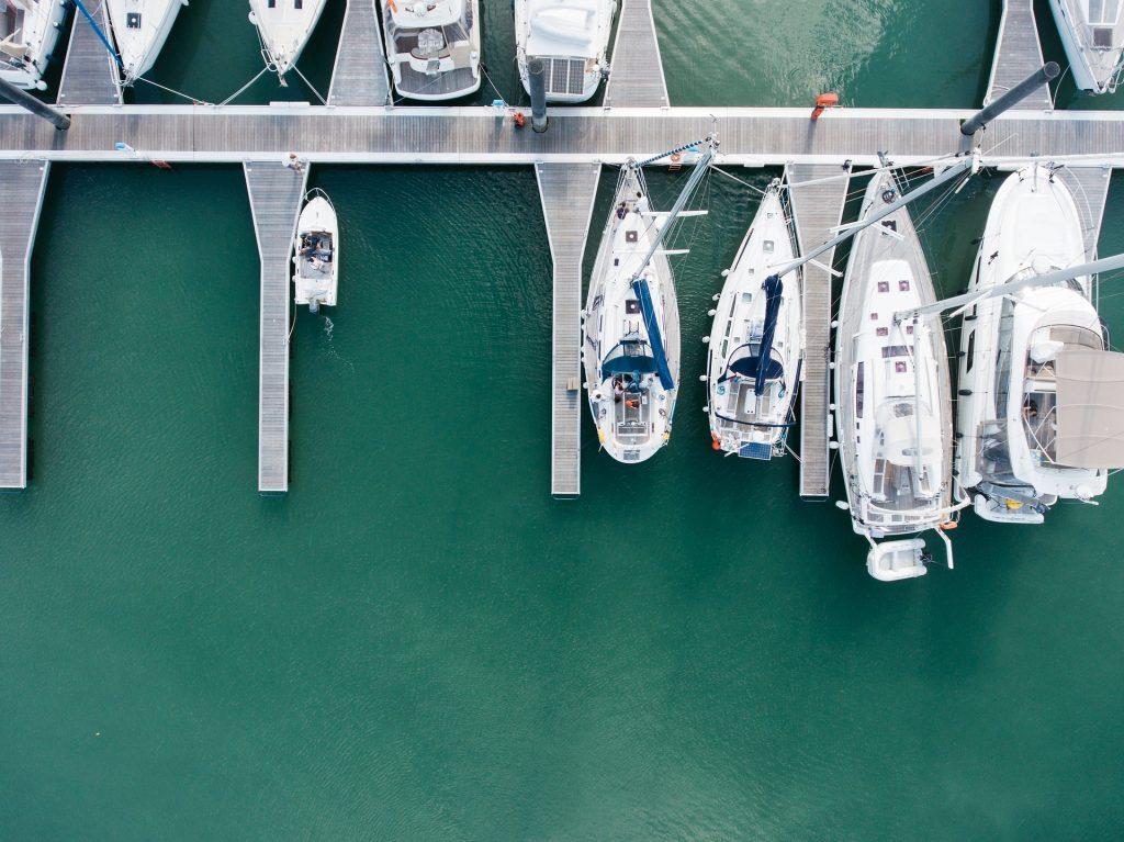 An einem Steg angdockte Segelboote und Yachten, aus der Vogelperspektive.