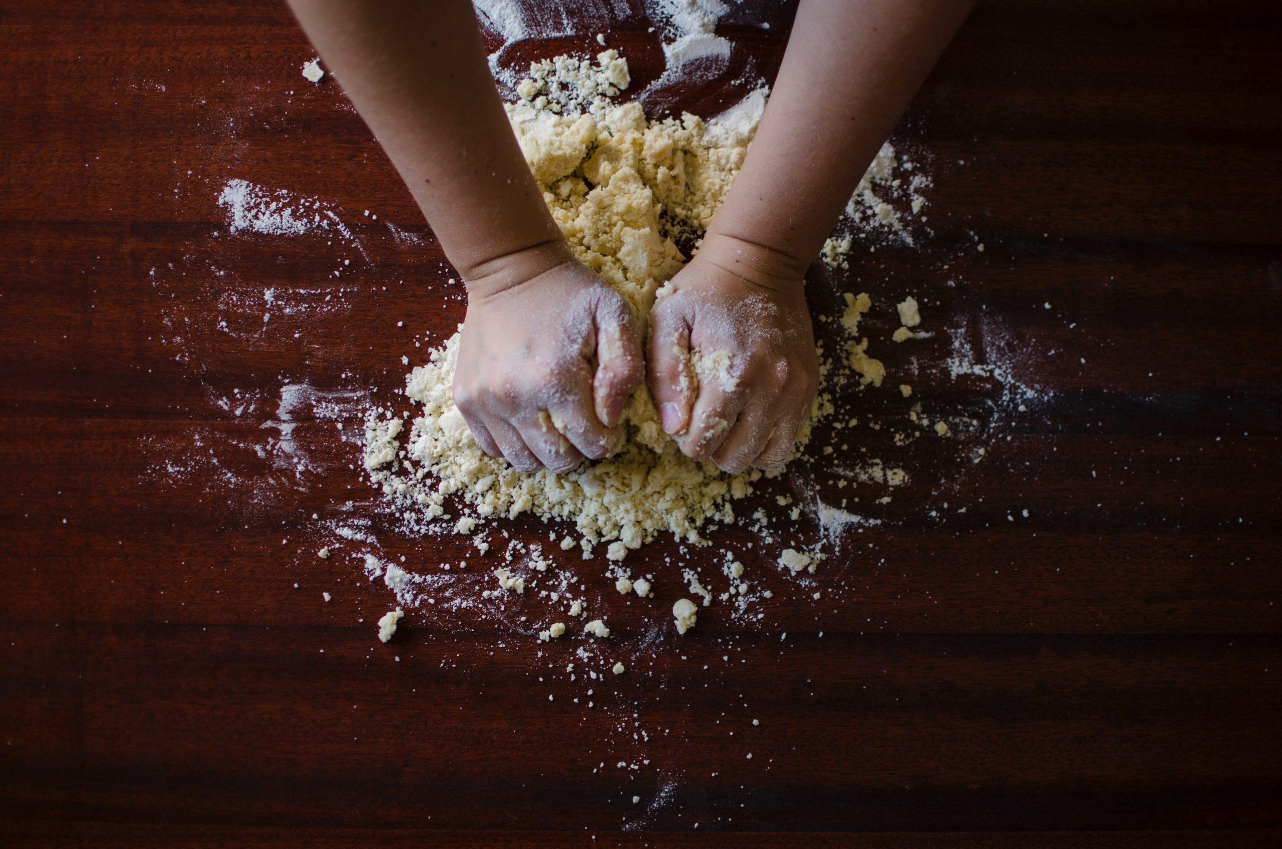 Mit den Händen wird ein Teig geknetet.
