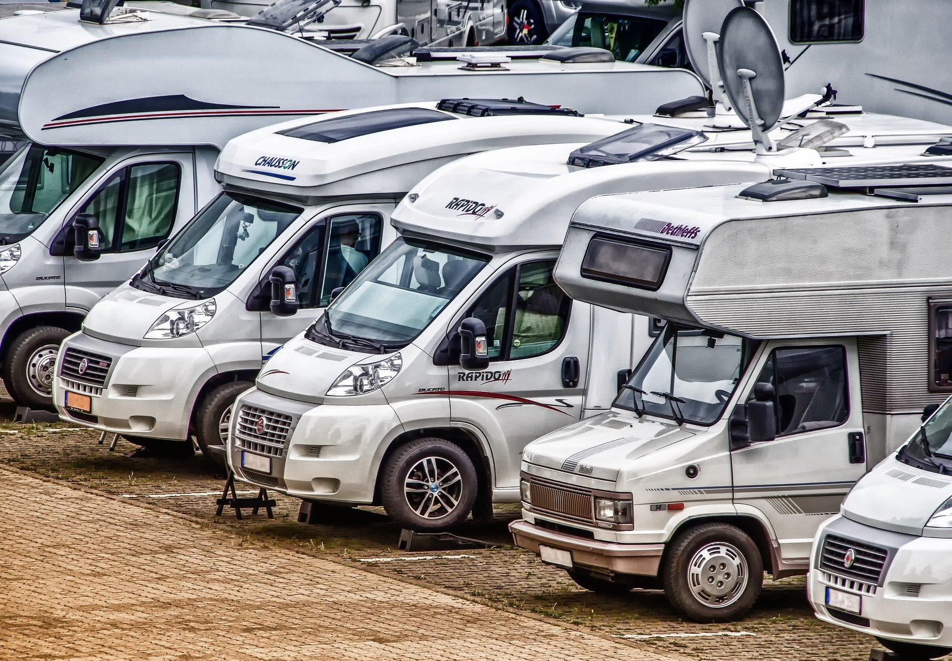Mehrere Wohnmobile parken in einer Reihe nebeneinander auf einem Campingplatz.