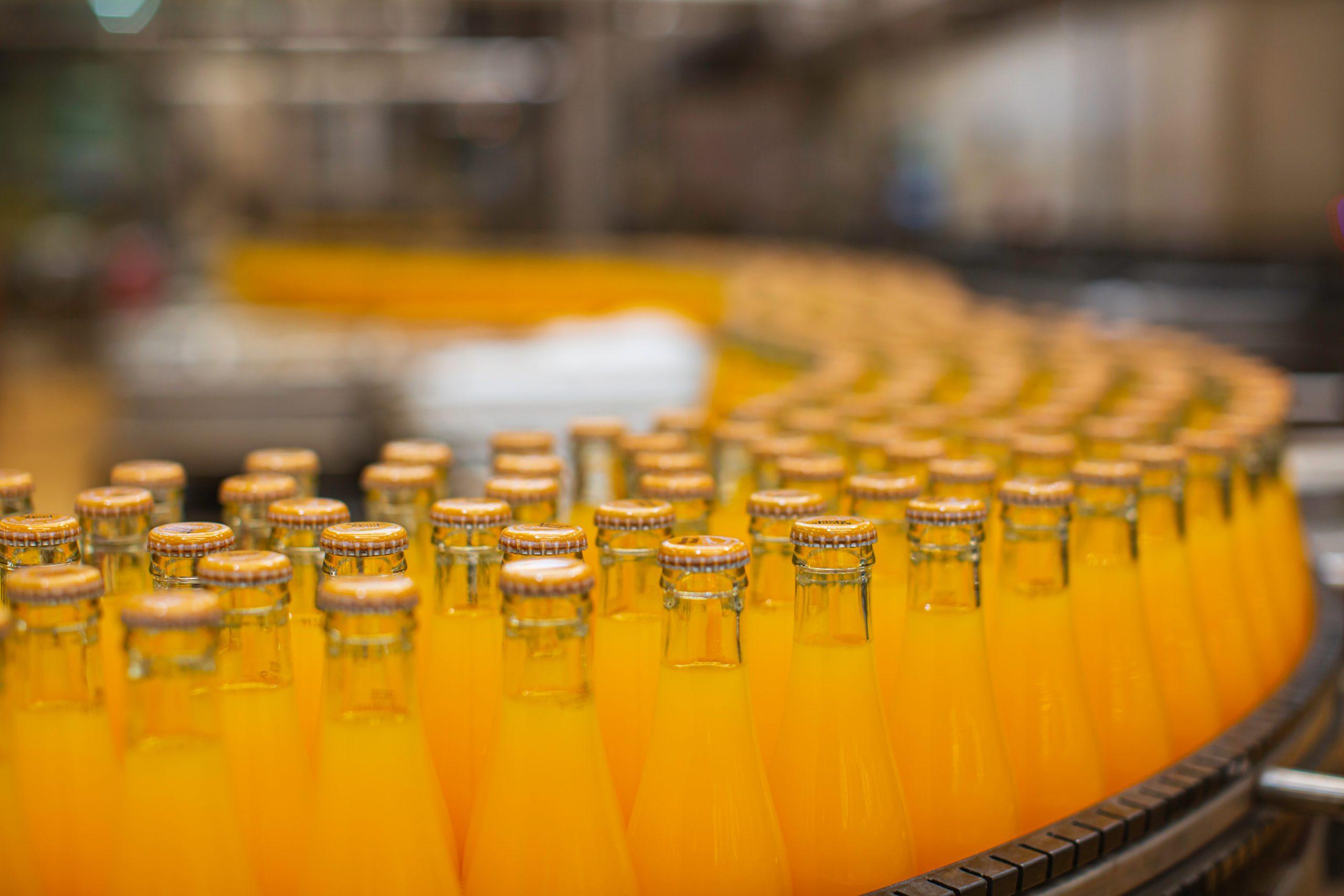 Ein Laufband voller Glasflaschen, die mit einem orangenen Getränk gefüllt sind.
