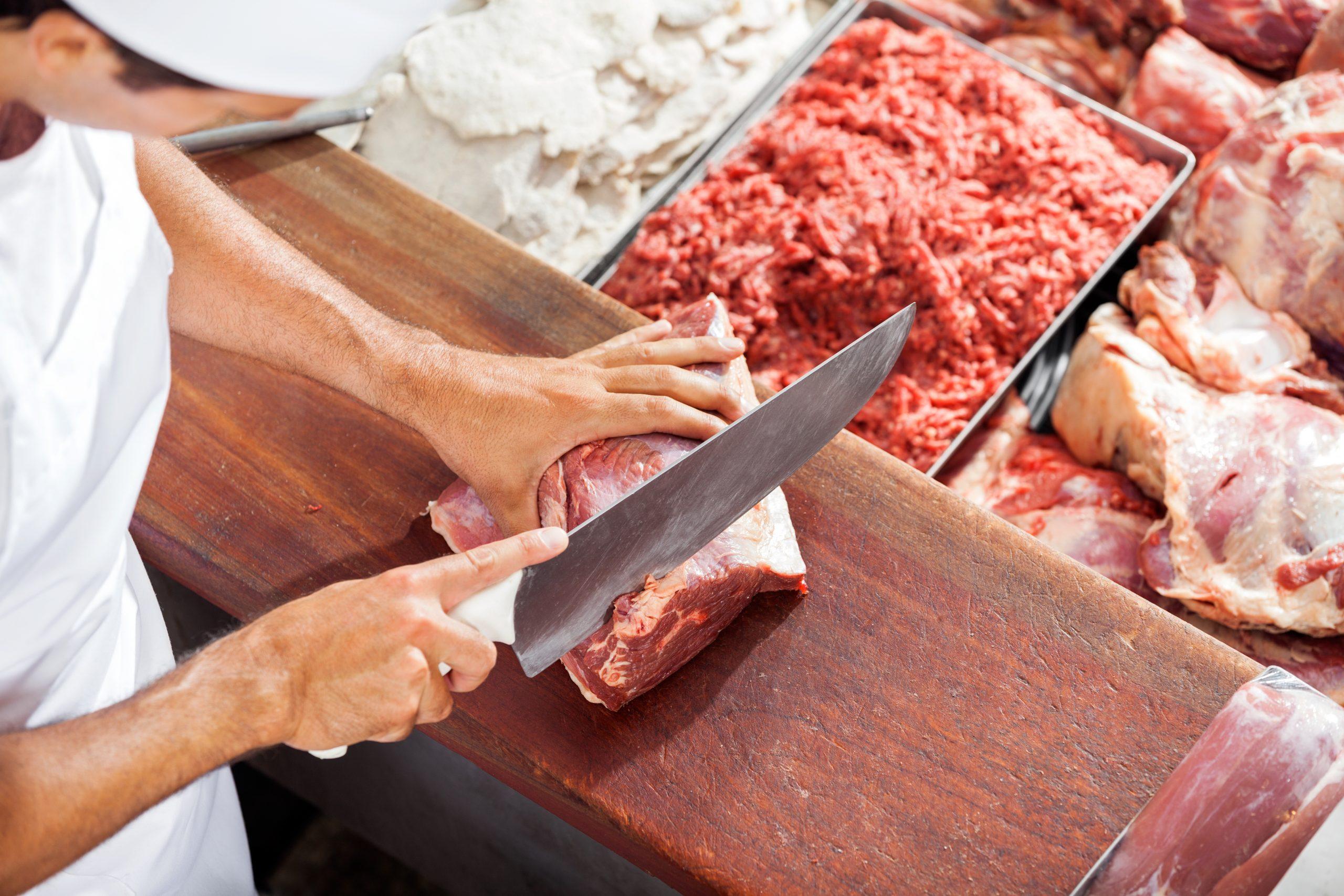 Ein Metzger schneidet Fleisch auf einer Theke.