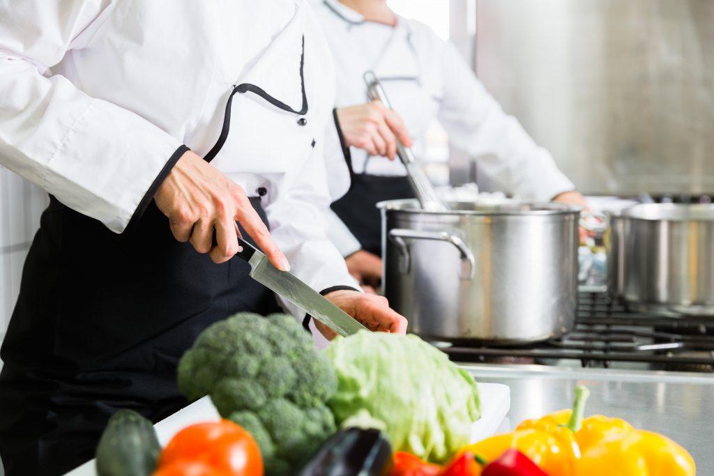 Zwei Köche stehen in einer Großküche. Eine Person rührt in einem Topf, während im Vordergrund frisches Gemüse geschnitten wird.