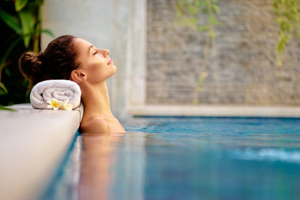 Eine Frau sitz entspannt in einem Pool.