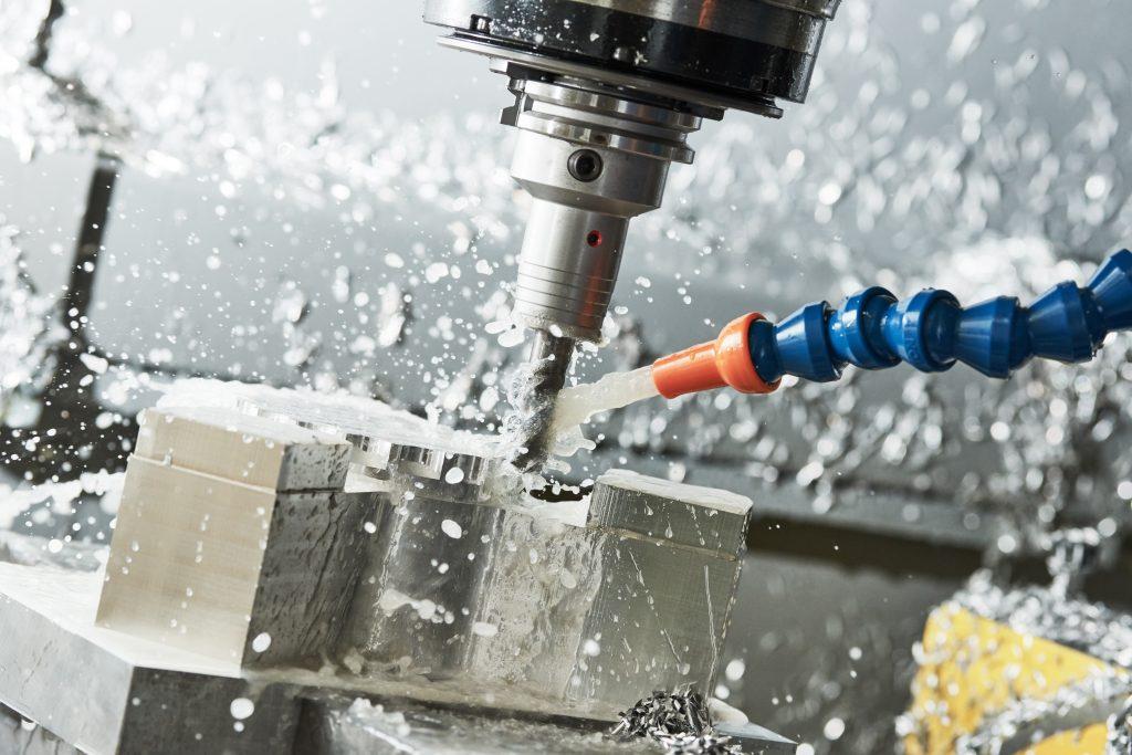 Mit einem Schlauch wird Wasser auf eine CNC-Fräse gespritzt, um sie zu kühlen.